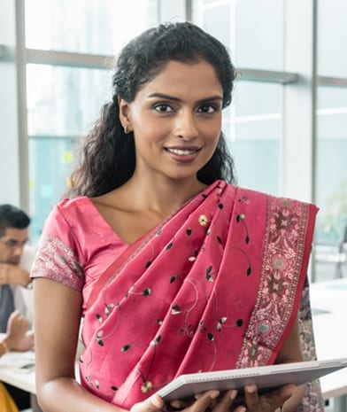 Confident Indian business woman looking at camera while holding a tablet in a modern meeting room