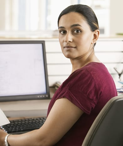 Portrait of young Asian businesswoman holding paper while using computer in office