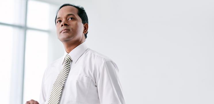 Portrait of pensive Indian businessman with digital tablet