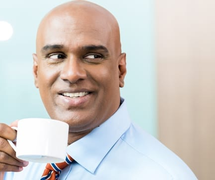 Indian Businessman with cup of coffee in office